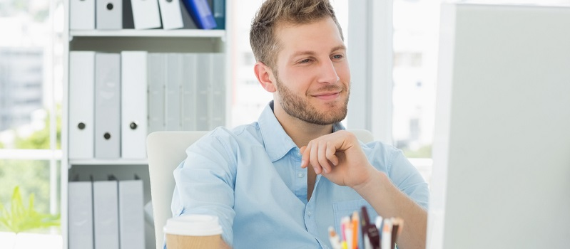 Smiling man working at his desk in creative office-landing page